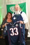 Linda Lewis, proud mom to Dion Lewis of the NE Patriots proudly presents Dr. Paul Byron with his winning Superbowl Jersey, which will be signed by Dion Lewis.